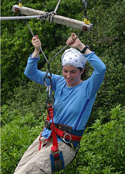 Student zip lining above the forest canopy