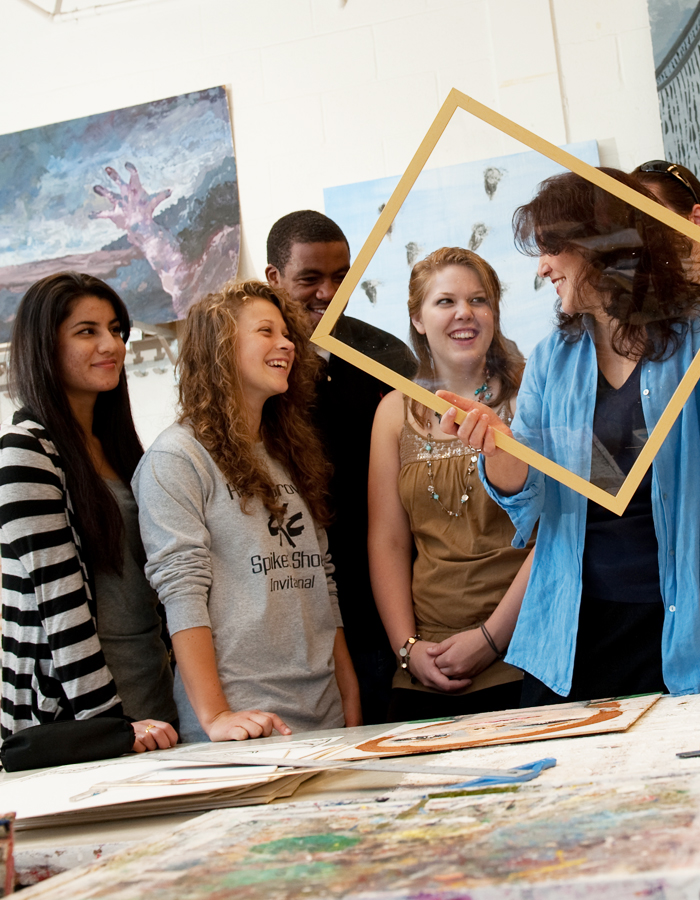 This is a picture of students enrolled in summer classes at Albright College speaking with a faculty member about an art piece.