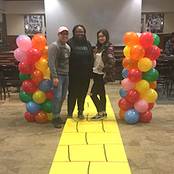 Photo of students with balloons and yellow path