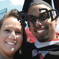 Graduate in fun glasses next to a woman