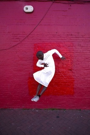 Woman jumping against a painted brick wall to showcase an installation by Maps Glover