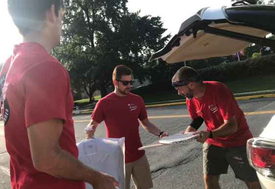 faculty and staff unload student cars