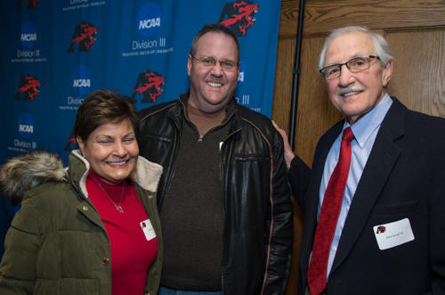 John Scholl smiling with two alumni