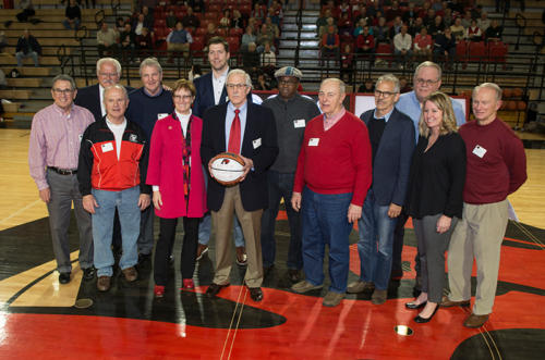 The president of Albright College standing with Alumni John Scholl and other alumni on the basketball court