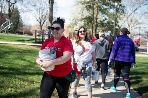 Alumni and volunteers carrying buckets