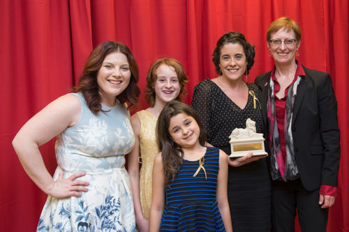 The president of Albright College with an award recipient and her children