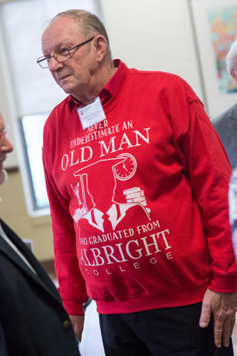 """An alumni in a sweater that says """"Never underestimate an old man who graduated from Albright College"""""""