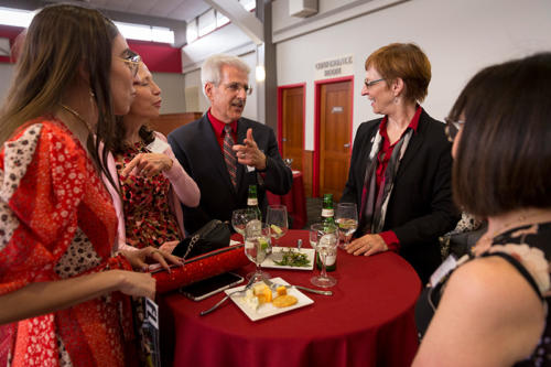 Alumni standing around a table with the President of Albright College