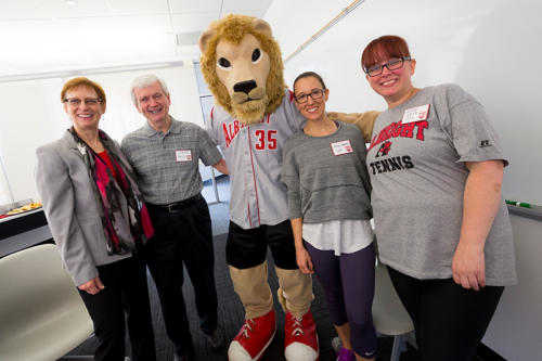 The president of Albright College smiling with alumni and the Albright College mascot