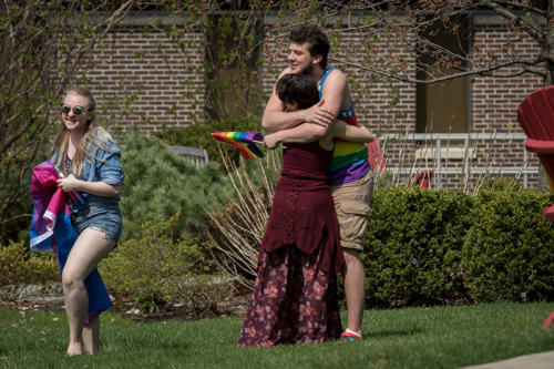 Two students holding gay pride flags hugging