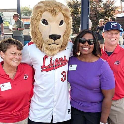 Alumni and family members standing with the Albright Lion