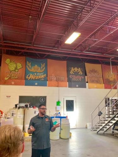 A tour guide speaking in front of the Sly Fox banners in the warehouse