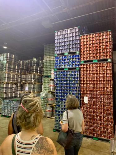 Stacks of beer cans and kegs in the brewery warehouse