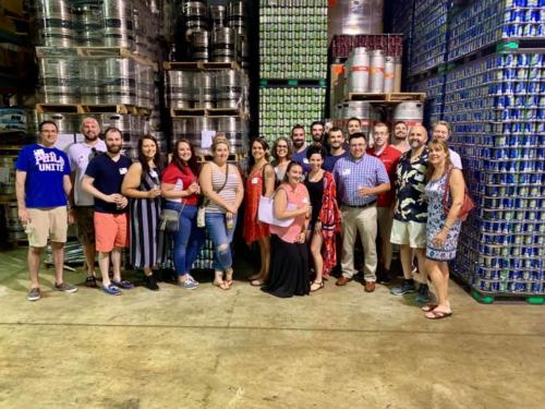 The tour attendees in front of the stacked cans