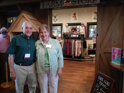 Two alumni standing next to the Farm Store
