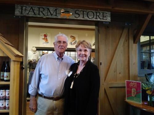 Two alumni standing in front of the Farm Store