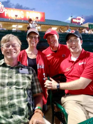 The president of Albright College smiling with faculty and attendee in the stands