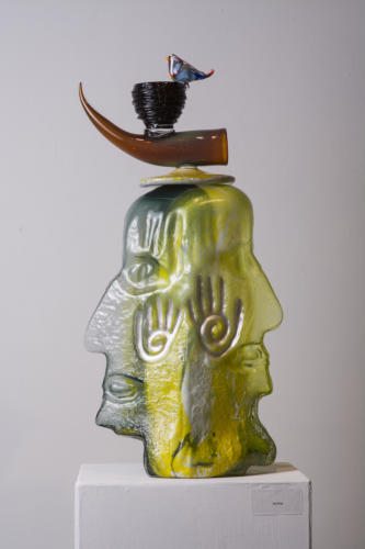 A green and yellow glass piece of two faces with a bird on it's head