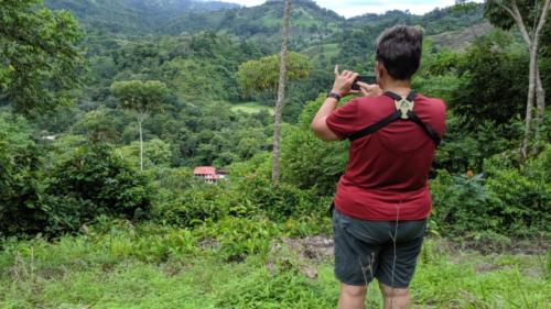 A trip member taking a photo of a landscape with their phone