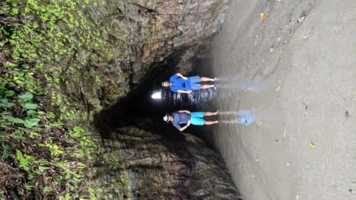 Two trip members standing in front of a cave