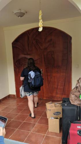 A trip member walking towards a set of carved wooden doors