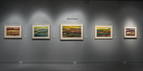 Five colorful pieces by Richard Hamwi displayed on the wall